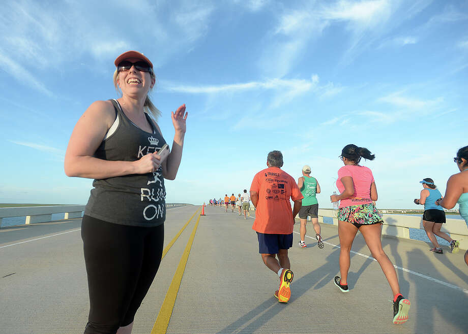 Elise Becker waves to runners as she cheers them on halfway across the bridge during the Sabine Causeway 5K in Port Arthur Friday. Runners and walkers made two laps on the Sabine Causeway Bridge, which runs from Texas to Louisiana. Photo taken Friday, August 21, 2015 Kim Brent/The Enterprise Photo: Kim Brent / Beaumont Enterprise