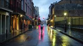 A woman walks in the middle of a street through the rain-soaked and deserted French Quarter of New Orleans in advance of Hurricane Katrina August 28, 2005. Hundreds of thousands of New Orleans residents fled inland as Katrina strengthened into one of the fiercest U.S. storms ever seen and barreled toward the low-lying Gulf Coast city