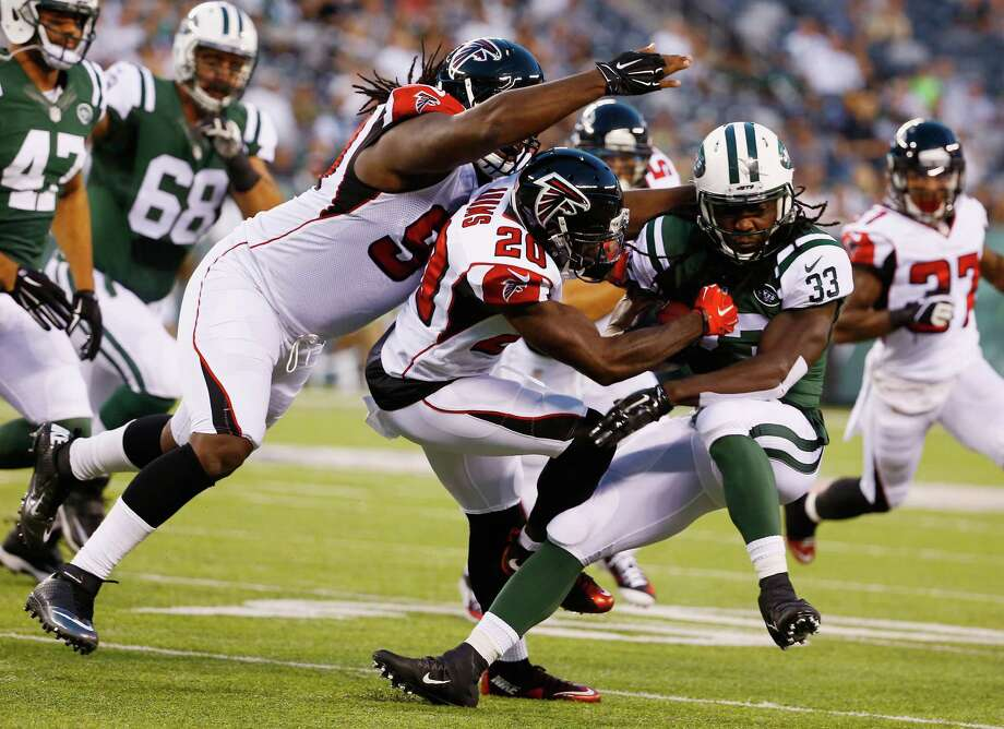 EAST RUTHERFORD, NJ - AUGUST 21: Phillip Adams #20 of the Atlanta Falcons tackles running back Chris Ivory #33 of the New York Jets during their pre season game at MetLife Stadium on August 21, 2015 in East Rutherford, New Jersey.  (Photo by Al Bello/Getty Images) ORG XMIT: 564374529 Photo: Al Bello / 2015 Getty Images