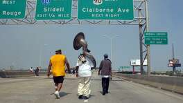 "Mark Smith, middle, walks toward an area where he was going to camp out, carrying along his tuba on a highway next to the Superdome in New Orleans on Friday, Sept. 2, 2005. ""If I leave this I might as well jump in the water myself,"" he said of his tuba. ""This is my livelihood."""