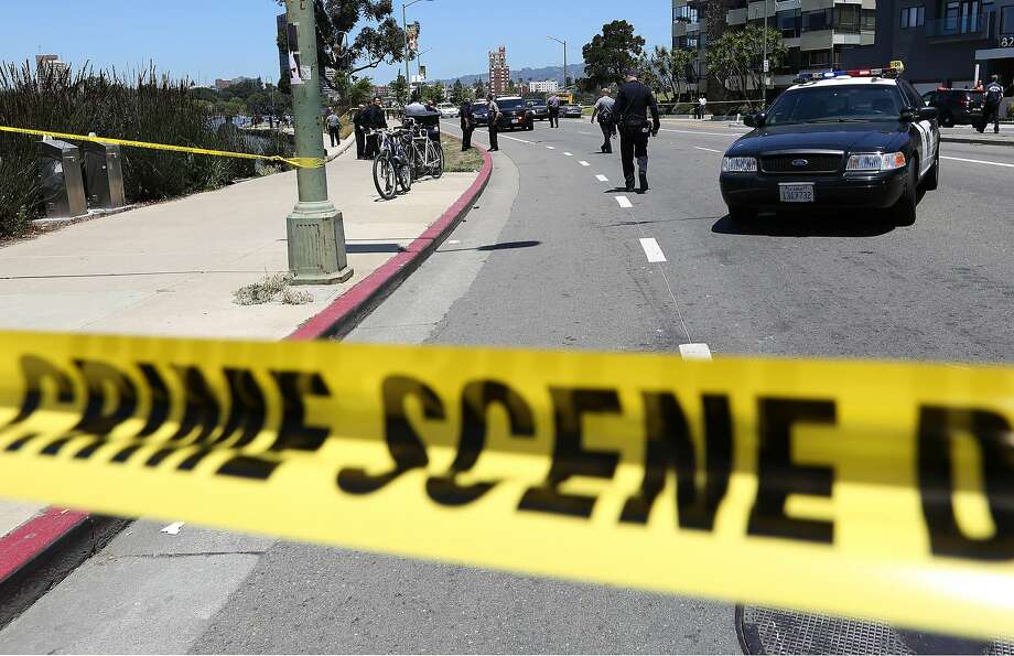 Oakland police investigate the scene of a shooting on Lakeshore Avenue in Oakland, Calif., on Friday, June 19, 2015. Three people shot five blocks from the NBA championship celebration for the Golden State Warriors in Oakland are in stable condition. Police say they received a call shortly after noon and found three male victims with gunshot wounds. (Jane Tyska/The Oakland Tribune via AP) Photo: Jane Tyska, Associated Press