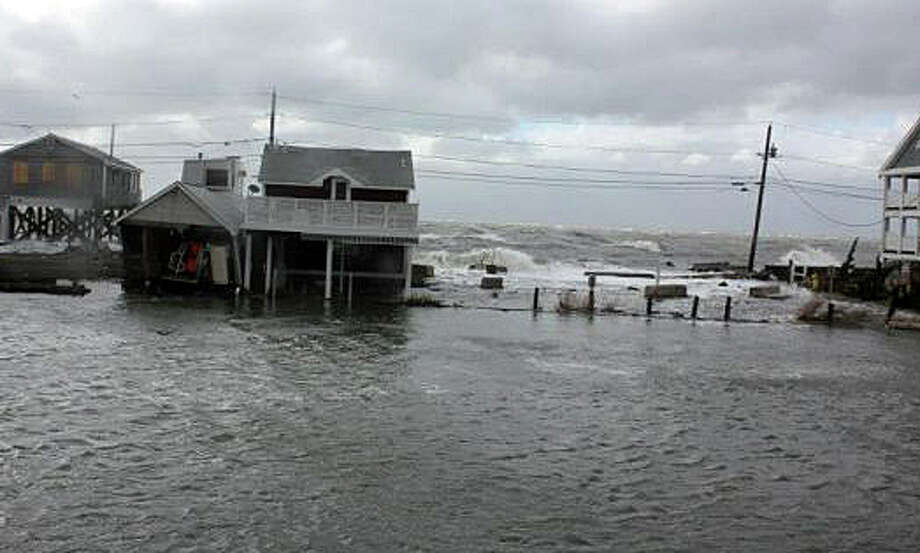 Long Island Sound waters ravage Fairfield Beach Road properties and flood the low-lying street during Superstorm Sandy in October 2012. Neighborhood residents, however, at a forum sponsored by the Flood and Erosion Control Board, were not supportive of a proposal to build a $5 million flood-prevention wall along the shoreline. Photo: File Photo / Fairfield Citizen