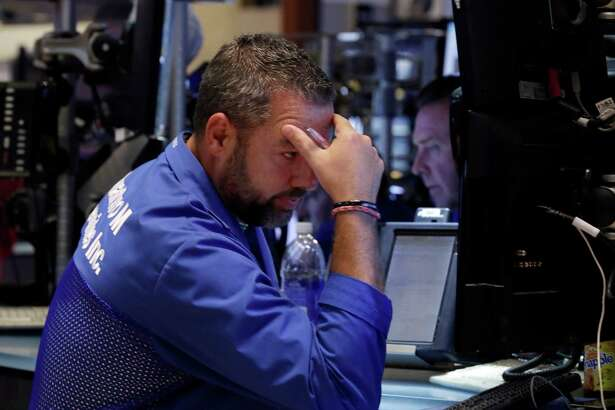 Trader Kevin Lodewick works on the floor of the New York Stock Exchange, Friday, Aug. 21, 2015. The Dow Jones industrial average has plunged more than 530 points and is in a correction amid a global sell-off sparked by fears about China's slowing economy. Oil tumbled below $40 per barrel for the first time since the financial crisis.