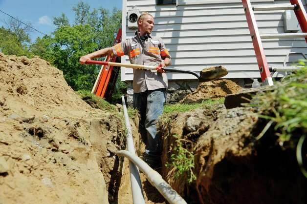 Jeff Hamblin with Apex Solar lays conduit to a garage at a home on Wednesday, Aug. 19, 2015, in Delmar, N.Y.  The home was getting solar panels on the house roof and the garage roof.  The home is being done through the Solarize Albany program.    (Paul Buckowski / Times Union) Photo: PAUL BUCKOWSKI / 00033062A