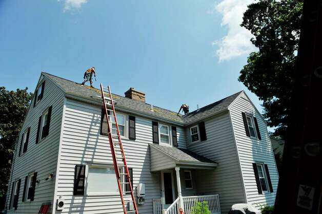 Rick Ortiz, left, roof foreman with Apex Solar and Steve Palmer, an installer, ready the roof for solar panels at a home on Wednesday, Aug. 19, 2015, in Delmar, N.Y.  The home is being done through the Solarize Albany program.    (Paul Buckowski / Times Union) Photo: PAUL BUCKOWSKI / 00033062A