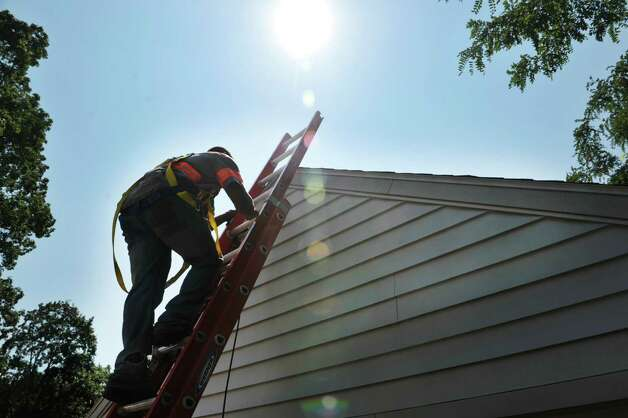 Everetton Newman with Apex Solar climbs up a ladder to the roof of a garage at a home on Wednesday, Aug. 19, 2015, in Delmar, N.Y.  The home is getting solar panels on the house roof and the garage roof.  The home is being done through the Solarize Albany program.    (Paul Buckowski / Times Union) Photo: PAUL BUCKOWSKI / 00033062A