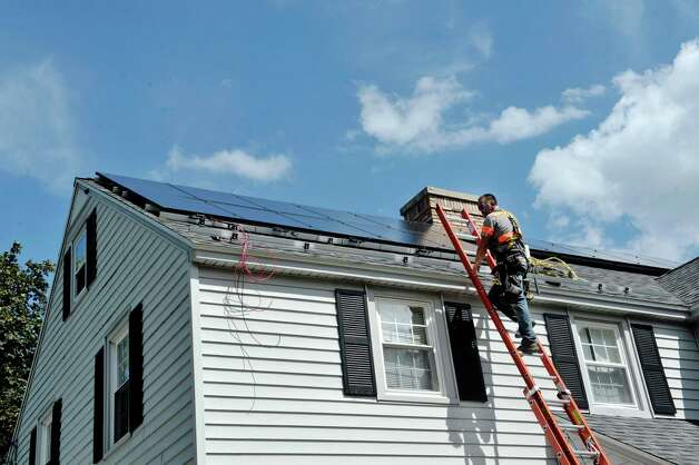 Jason Hay with Apex Solar checks over some solar panels on the roof at a home on Thursday, Aug. 20, 2015, in Delmar, N.Y.  The home is being done through the Solarize Albany program.    (Paul Buckowski / Times Union) Photo: PAUL BUCKOWSKI / 00033062A