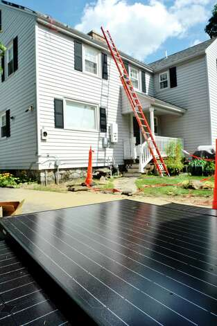 A stack of solar panels are seen in the foreground as workers from Apex Solar install panels on the roof at a home on Thursday, Aug. 20, 2015, in Delmar, N.Y.  The home is being done through the Solarize Albany program.    (Paul Buckowski / Times Union) Photo: PAUL BUCKOWSKI / 00033062A