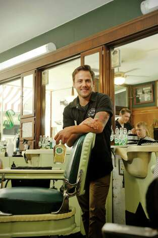 Patsy's Barber Shop barber Michael Richmond poses for a photo holding a bottle the shop's home made bay rum aftershave on Thursday, Aug. 20, 2015, in Albany, N.Y.  The shop makes various home made products that they use and sell. The bay rum aftershave is the recipe of the shop owner, William Tragedy Yager's great grandfather who worked at the shop from 1938 to 1942.     (Paul Buckowski / Times Union) Photo: PAUL BUCKOWSKI / 00033062A