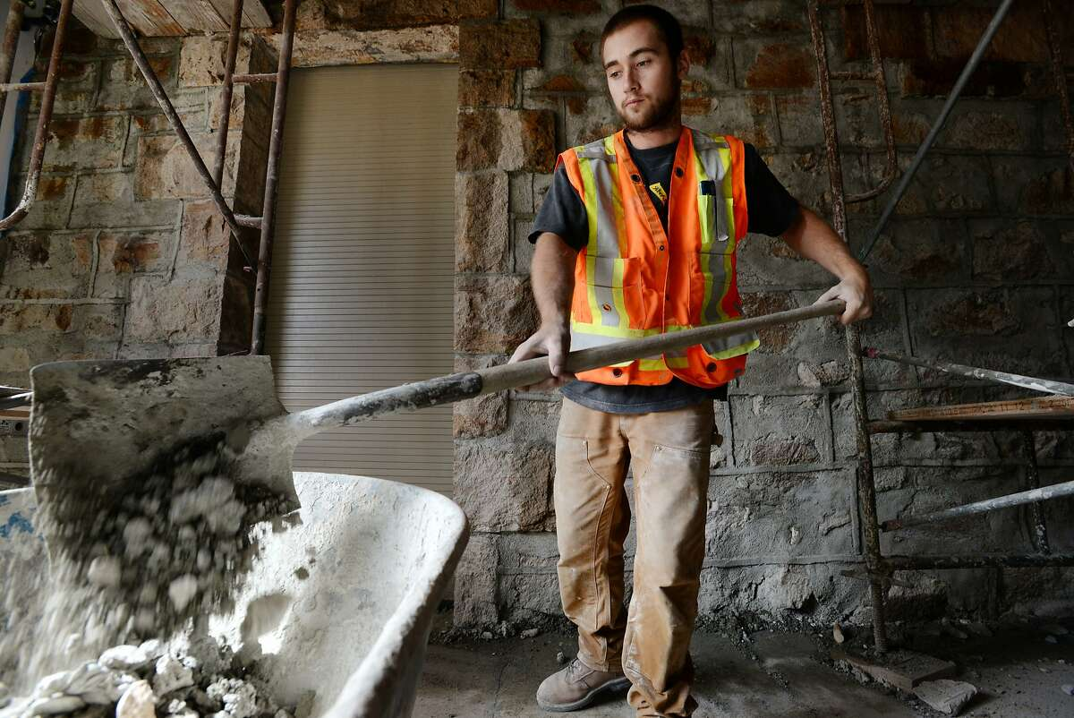Construction worker Cody Hayes, 22, cleaning up debris next to a 3-story wall in the lobby of The Hess Collection winery in Napa that had been damaged in the Napa quake. The winery plans to have all construction completed by mid-September. August 22, 2015.