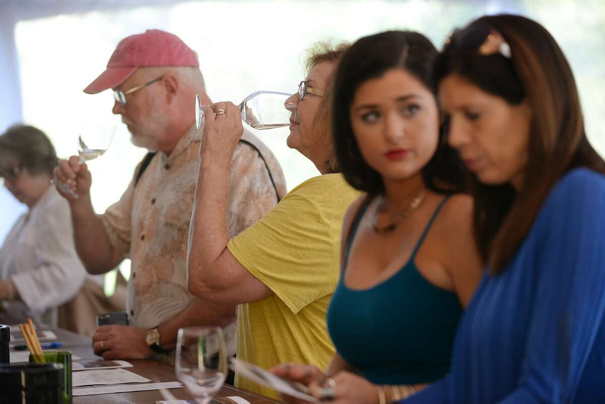 Devon Scheef, in yellow, tasting wine with Gary Coon, both from Westlake Village, California at The Hess Collection winery's temporary tasting room in Napa which was set up about a month ago while the permanent tasting room is under construction after being damaged in the Napa quake last year. August 22, 2015.