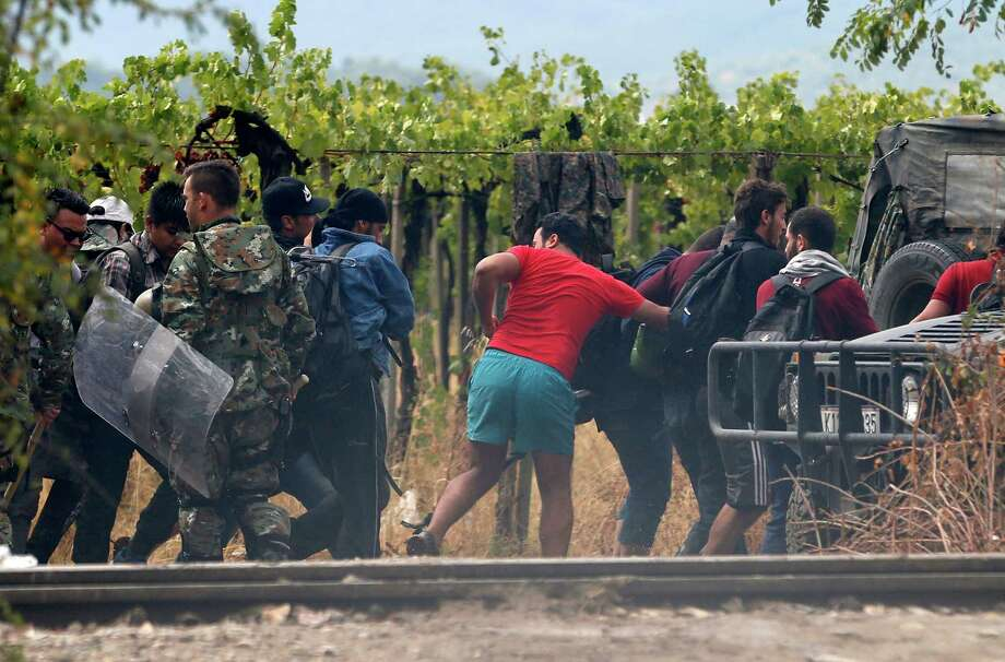 Migrants run by Macedonian riot police officer on the border line with Greece, near the train station of Idomeni, northern Greece, Saturday, Aug. 22, 2015. About 39,000 people have been registered as passing through Macedonia in the past month, twice as many as the month before.  (AP Photo/Darko Vojinovic) Photo: Darko Vojinovic, STF / AP