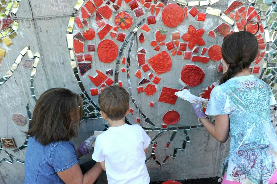 Anne Savage, left, and her children Alex and Katie Myers join others as Capital Roots (formerly Capital District Community Gardens) invited the community to the Urban Grow Center in Troy to install a 400 square foot mosaic mural depicting a cityscape bursting with fresh fruit and vegetables designed by artist Jillian Hirsch on Saturday Aug. 22, 2015 in Troy, N.Y.  (Michael P. Farrell/Times Union) Photo: Michael P. Farrell / 00033054A