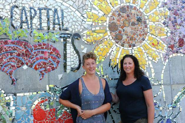 Project artist Jillian Hirsch, left, and Amy Klein executive director join others as Capital Roots (formerly Capital District Community Gardens) invited the community to the Urban Grow Center in Troy to install a 400 square foot mosaic mural depicting a cityscape bursting with fresh fruit and vegetables designed by artist Jillian Hirsch on Saturday Aug. 22, 2015 in Troy, N.Y.  (Michael P. Farrell/Times Union) Photo: Michael P. Farrell / 00033054A