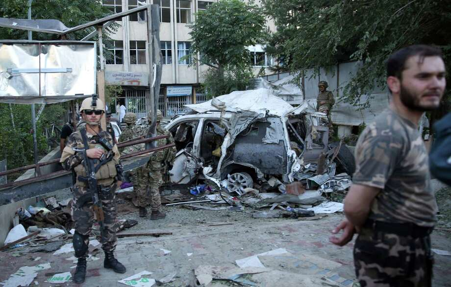 Afghan security forces and British soldiers inspect the site of a suicide attack in the heart of Kabul, Afghanistan. The bomber attacked a NATO convoy in a crowded capital neighborhood.  Photo: Massoud Hossaini, STF / AP