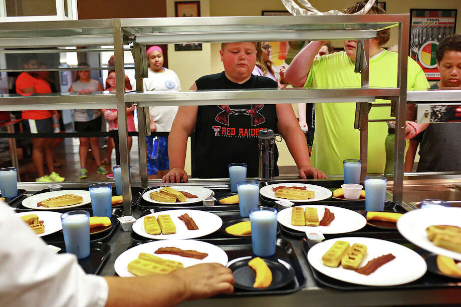 "John Davis, 12, of Amarillo, waits to take his plate for breakfast, the campers' first breakfast at the camp, at Camp Shane in San Antonio on Sunday, June 14, 2015. Davis lost 16 pounds in the first two weeks of camp but was homesick  and left before the end of the third week. ""I came here because I wanted to lose weight because when I grow up I want to be in the Navy Seals,"" John said. Photo: Lisa Krantz, Staff / SAN ANTONIO EXPRESS-NEWS / SAN ANTONIO EXPRESS-NEWS"