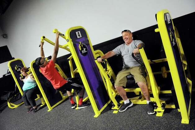 Danny Poleto of Colonie, right, and his son Vinny Poleto, 16, center try out the exercise equipment during the grand opening of the Lord's Gym on Saturday, Aug. 22, 2015, at The Bridge Christian Church in Schenectady, N.Y. (Cindy Schultz / Times Union) Photo: Cindy Schultz / 00032810A