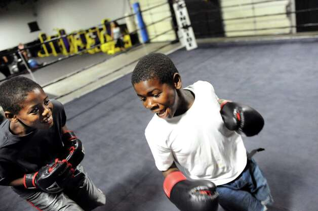 Deandre Taylor, 11, left, chases his brother Devanty Taylor, 8, as they spar in the boxing ring during the grand opening of the Lord's Gym on Saturday, Aug. 22, 2015, at The Bridge Christian Church in Schenectady, N.Y. (Cindy Schultz / Times Union) Photo: Cindy Schultz / 00032810A