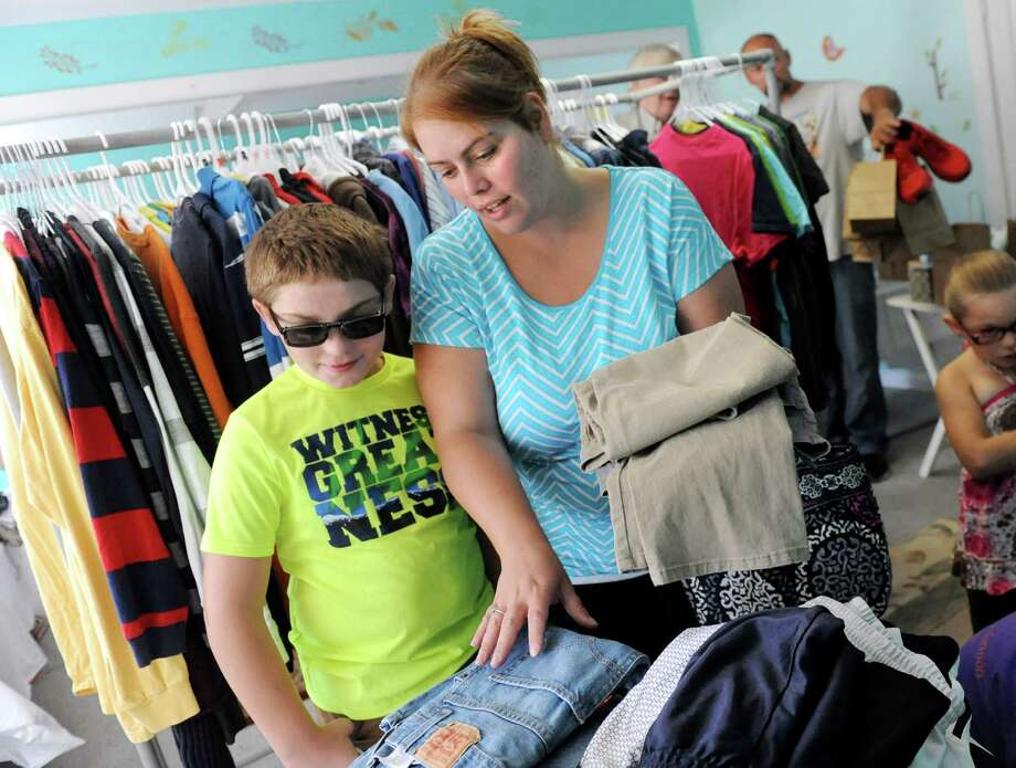 Dustyn Snyder, 10, of Watervliet, left, and his mother Andrea Snyder select pants for him during the Pay It Forward Together sponsored Back-to-School Closet on Saturday, Aug. 22, 2015, at Bethany Presbyterian Church in Menands, N.Y. (Cindy Schultz / Times Union) Photo: Cindy Schultz / 00033044A