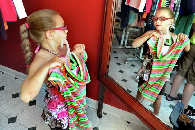 Abigail Snyder, 7, of Watervliet sizes up an outfit during the Pay It Forward Together sponsored Back-to-School Closet on Saturday, Aug. 22, 2015, at Bethany Presbyterian Church in Menands, N.Y. (Cindy Schultz / Times Union) Photo: Cindy Schultz / 00033044A