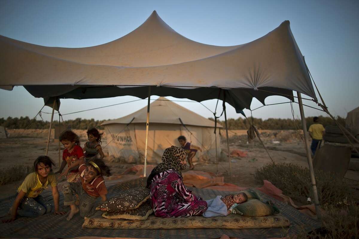 A Syrian refugee sits on the ground next to her child to escape the heat trapped inside their tent, at an informal tented settlement near the Syrian border on the outskirts of Mafraq, Jordan, Saturday, Aug. 22, 2015.