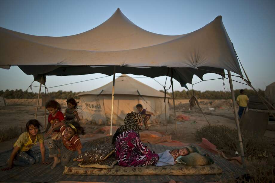 A Syrian refugee sits on the ground next to her child to escape the heat trapped inside their tent, at an informal tented settlement near the Syrian border on the outskirts of Mafraq, Jordan, Saturday, Aug. 22, 2015.  Photo: Muhammed Muheisen, Associated Press