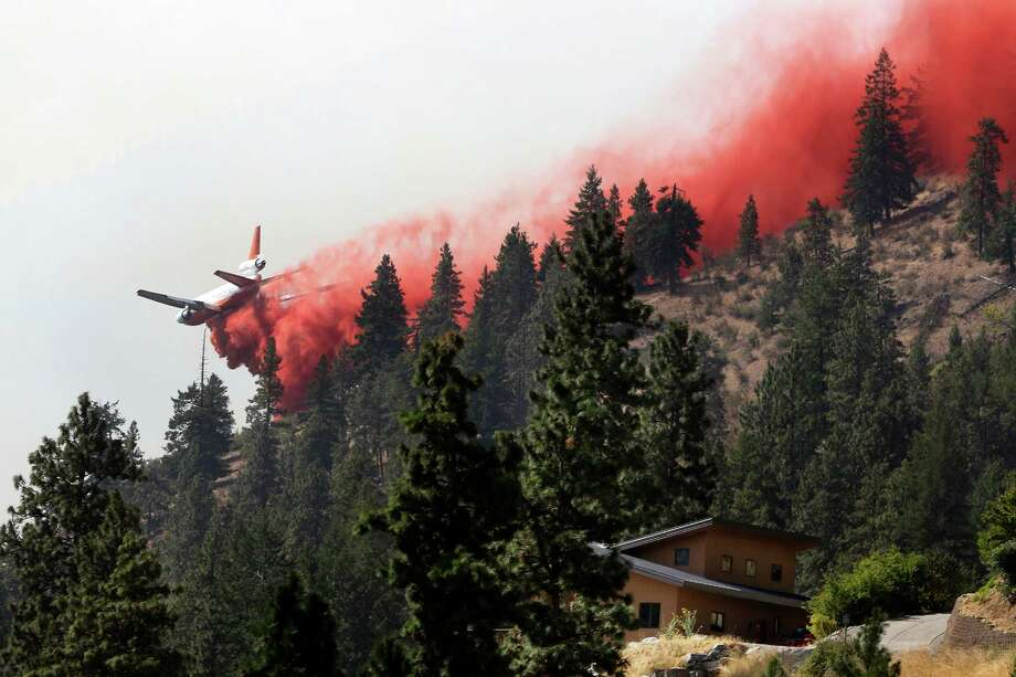 A tanker airplane drops fire retardant on a hillside above a neighborhood on Lake Chelan in north-central Washington state as  wildfires    expand  across the arid land  and tax     firefighters. Photo: Genna Martin / Associated Press / The Herald