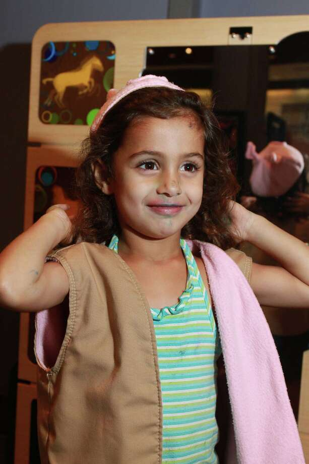 """Seyana Shah, 4, tries on a hat at """"Animal Motion,"""" which allows kids to dress as animals and play in the mirror, for part of the Health Museum's Summer Shake-off, Saturday, August 22, in Houston.  Photo: Gary Fountain / Copyright 2015 by Gary Fountain"""