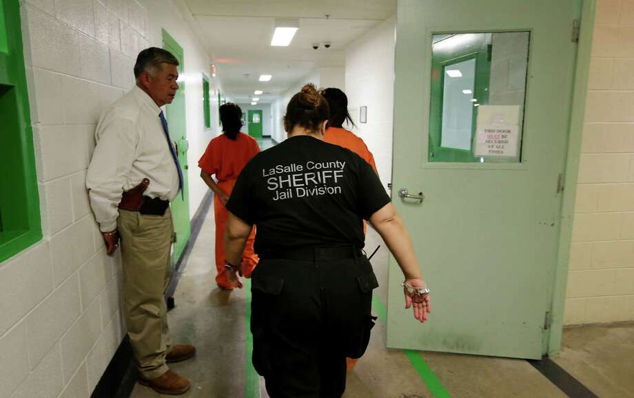 La Salle County Sheriff Miguel Rodriguez, left, monitors the transfer of a pair of inmates by a detention officer earlier this month at the La Salle County Detention Center in Encinal. The detention facility is at about half capacity and losing money. Photo: Kin Man Hui, Staff / ©2015 San Antonio Express-News