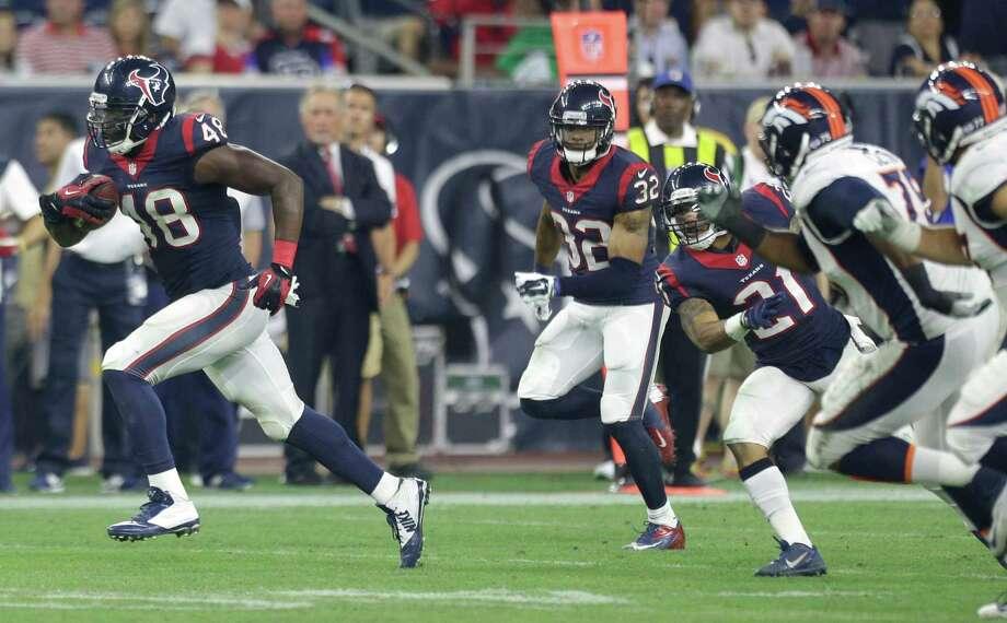 Texans linebacker Kourtnei Brown, left, returns an interception of Broncos quarterback Brock Osweiler for a 69-yard touchdown during the third quarter Saturday. Photo: Brett Coomer, Staff / © 2015  Houston Chronicle