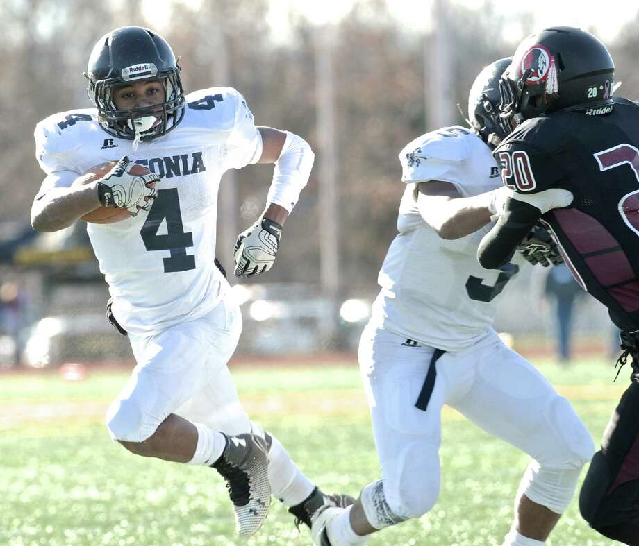 Ansonia's Tajik Bagley (4) goes around a block by team mate Tyler Bailey (5) on Valley Regional's Evan Smith (20) and runs into the end zone for a touch down during the Connecticut Class S Large state football championship game between Valley Regional/Old Lyme and Ansonia high schools, on Saturday, December 13, 2014, played at Veterans memorial Stadium, in New Britain, Conn. Photo: H John Voorhees III / H John Voorhees III / The News-Times