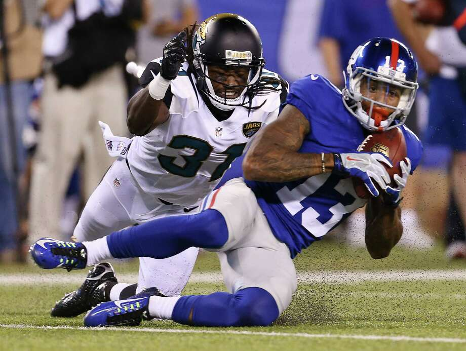 Jacksonville Jaguars defensive back Davon House (31) tackles New York Giants wide receiver Odell Beckham (13) who was making a sliding catch in front of him during the first half of a preseason NFL football game Saturday, Aug. 22, 2015, in East Rutherford, N.J. (AP Photo/Adam Hunger) ORG XMIT: ERU106 Photo: Adam Hunger / FR110666 AP