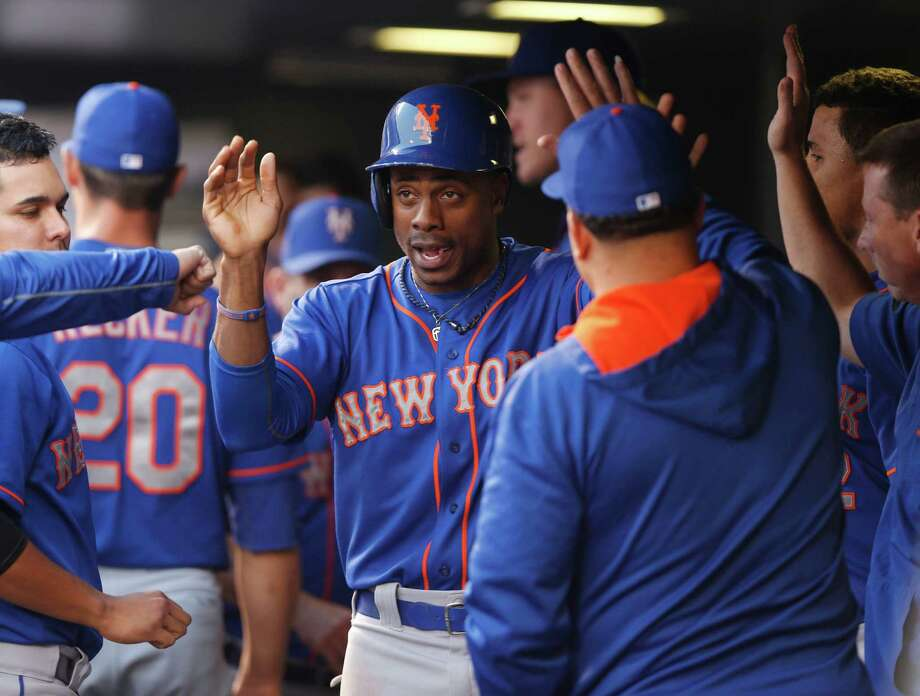New York Mets' Curtis Granderson, center, is congratulated by teammates after scoring from third base on a double play hit into by Juan Uribe against the Colorado Rockies in the third inning of a baseball game Saturday, Aug. 22, 2015, in Denver. (AP Photo/David Zalubowski) ORG XMIT: CODZ116 Photo: David Zalubowski / AP
