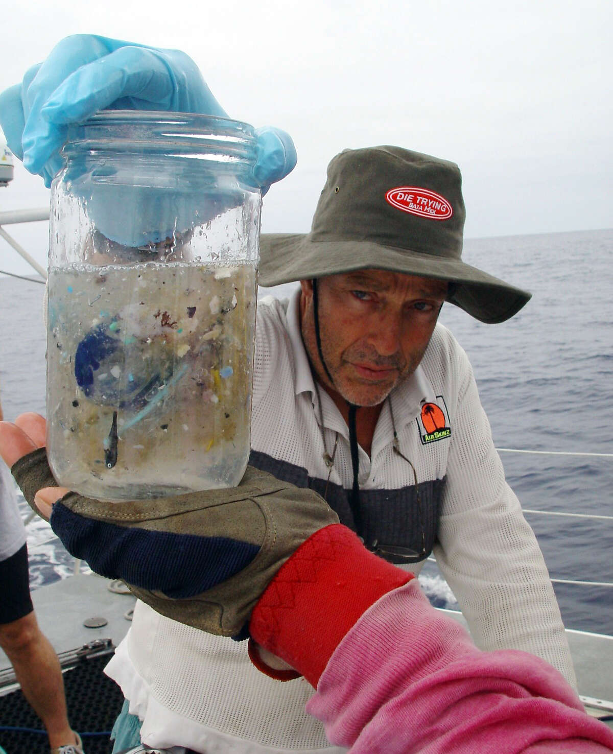 Marine researcher Charles Moore holds a sample of ocean water from the North Central Pacific Gyre that contains small pieces of plastic.