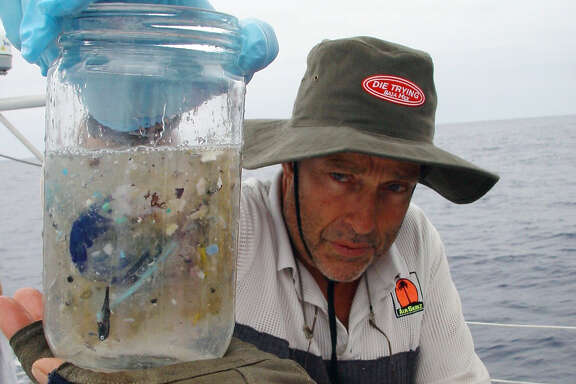 oceantrash30_ph.JPG  This handout picture shows marine researcher Charles Moore on an expedition in the Pacific Ocean sometime between July through September of 2002. He holds a sample of ocean water from the North Central Pacific Gyre  that contains small pieces of plastic. Moore, who works at the Long Beach-based Algalita Marina Research Foundation, has been studying the stew of plastic and marine debris floating in the ocean.  Matt Cramer / Algalita Marina Research / Courtesy to The Chronicle  Ran on: 10-30-2007 Researcher Charles Moore, shown on an expedition in the Pacific in 2002, holds a water sample from the North Pacific Gyre that contains small pieces of plastic taken from the mass of garbage. Ran on: 10-30-2007 Researcher Charles Moore, shown on an expedition in the Pacific in 2002, holds a water sample from the North Pacific Gyre that contains small pieces of plastic taken from the mass of garbage. Ran on: 11-03-2007 Researcher Charles Moore, shown on an expedition in the Pacific in 2002, holds a water sample from the North Pacific Gyre that contains small pieces of plastic taken from the mass of garbage.