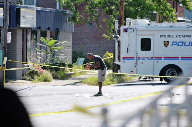 An investigator videotapes evidence cards on the street as Troy Police work at the scene where two officers were shot Saturday night, on Sunday, Aug. 23, 2015, in Troy, N.Y.    (Paul Buckowski / Times Union)