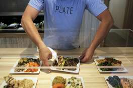 """Manager Jon Goodman sets the food display in preparation for the dinner rush at Plate, a take-out restaurant in San Francisco, on Thursday, Aug. 13, 2015. """"Our whole thing is to make eating healthy as convenient as possible."""" Walker says. """"We are trying to be kinder to the earth, all of the plates are reusable."""""""