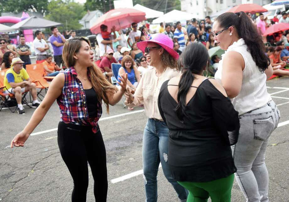 Danbury residents, from left, Ivetth Izquierdo, Guadalupe Guiterrez, Sueni Basurto and Raquel Urena dance to international music at the Summer Fiesta Festival at the DOMUS Foundation in Stamford, Conn. Sunday, Aug. 23, 2015.  The festival featured many international music artists and dance acts, as well as games and activities for kids.  The evening culminated with performance of the Native Instrument Academy Summer Camp Grand Community Choir. Photo: Tyler Sizemore, Hearst Connecticut Media / Greenwich Time