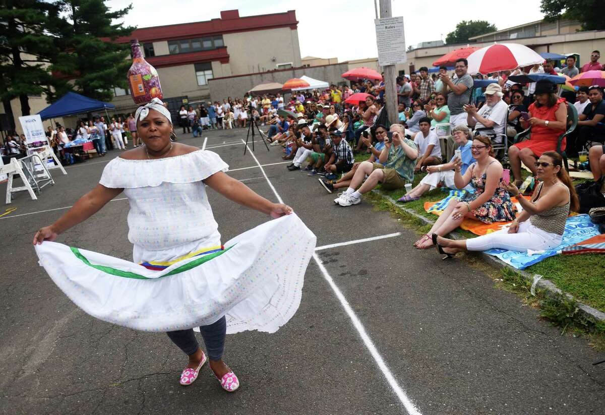 Kelly San Clemente, of Port Chester, N.Y., performs a dance act balancing a jug on her head at the Summer Fiesta Festival at the DOMUS Foundation in Stamford, Conn. Sunday, Aug. 23, 2015. The festival featured many international music artists and dance acts, as well as games and activities for kids. The evening culminated with performance of the Native Instrument Academy Summer Camp Grand Community Choir.