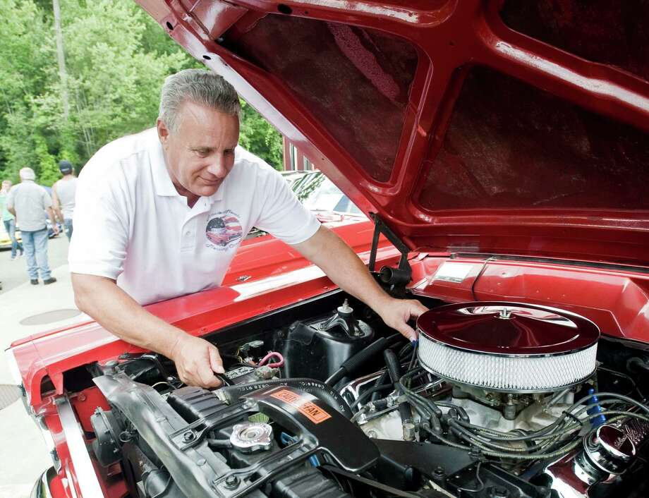 Carl Bock, of Danbury, adjusts part of the engine on his 1967 Mercury Comet GT on Sunday at the fourth annual Candlewood East Marina Car Show. The event is a fundraiser for the Leap of Faith Adaptive Skiers with works with veterans and the disabled. Photo: Scott Mullin / For Hearst Connecticut Media / The News-Times Freelance