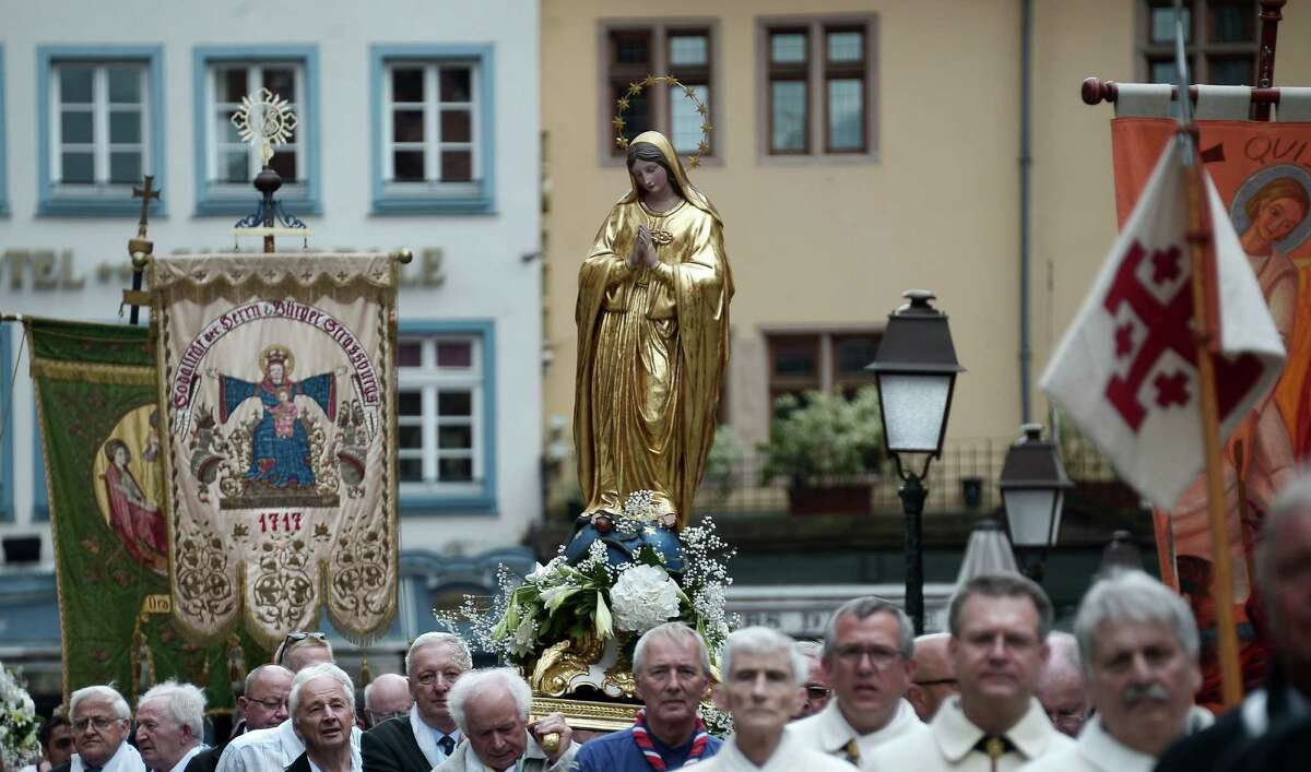 Faithfuls carry the statue of the Virgin Mary as they take part in a religious procession on the Feast of the Assumption in the streets of Strasbourg, eastern France on August 15, 2015 .