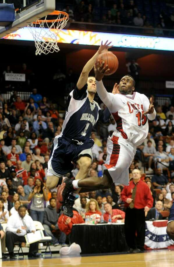 Central's #15 Jerome Parkins sends up the ball for two as Hillhouse's #1 Freddie Wilson tries to block, during Class L state championship action at Mohegan Sun Arena in Uncasville, Conn. on Saturday Mar. 20, 2010. Photo: Christian Abraham / Connecticut Post