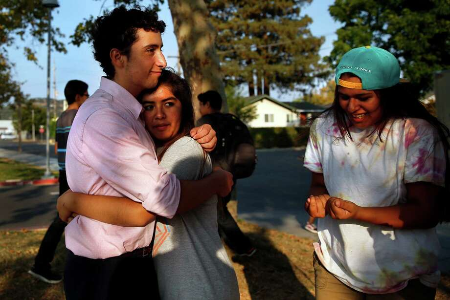 Nicholas Dillon, whose pelvis was broken when a chimney fell on him during the 2014 earthquake, embraces his friend Monica Hernandez with Juliana Silva nearby outside New Technology High School in Napa. Photo: Scott Strazzante / Scott Strazzante / The Chronicle / ONLINE_YES