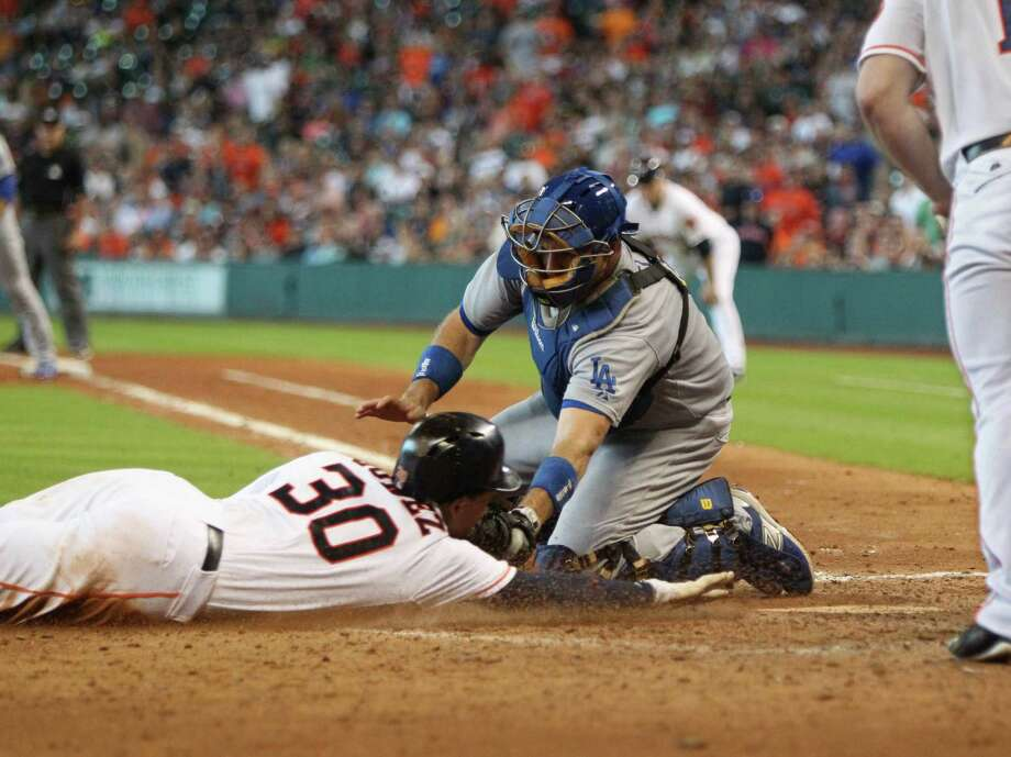 After taking measure of Clayton Kershaw's delivery, the Astros' Carlos Gomez (30) is out trying to steal home, ending Sunday's sixth inning. Replays confirmed the glove of Dodgers catcher A.J. Ellis brushed Gomez's chin. Photo: Gary Coronado, Staff / © 2015 Houston Chronicle