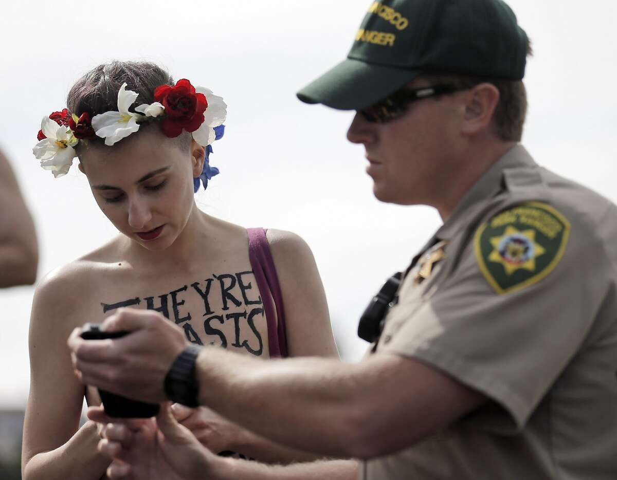 San Francisco Parks Dept Officer Gilmore shows Chelsea Ducote the park ordinance prohibiting women going topless at Dolores Park in San Francisco, Calif., on Sunday, August 23, 2015. The group GoTopless.org is organized Go Topless Day on the Sunday closest to Women's Equality Day, Aug 26. It is indeed on Aug 26, 1920 that women earned their right to vote on the basis of Gender Equality. In 1971, the US Congress has made Aug 26 into a nationally recognized date and named it