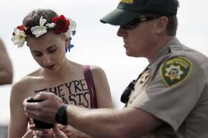"""San Francisco Parks Dept Officer Gilmore shows Chelsea Ducote the park ordinance prohibiting women going topless at Dolores Park in San Francisco, Calif., on Sunday, August 23, 2015. The group GoTopless.org is organized Go Topless Day on the Sunday closest to Women's Equality Day, Aug 26. It is indeed on Aug 26, 1920 that women earned their right to vote on the basis of Gender Equality. In 1971, the US Congress has made Aug 26 into a nationally recognized date and named it """"Women's Equality Day."""""""