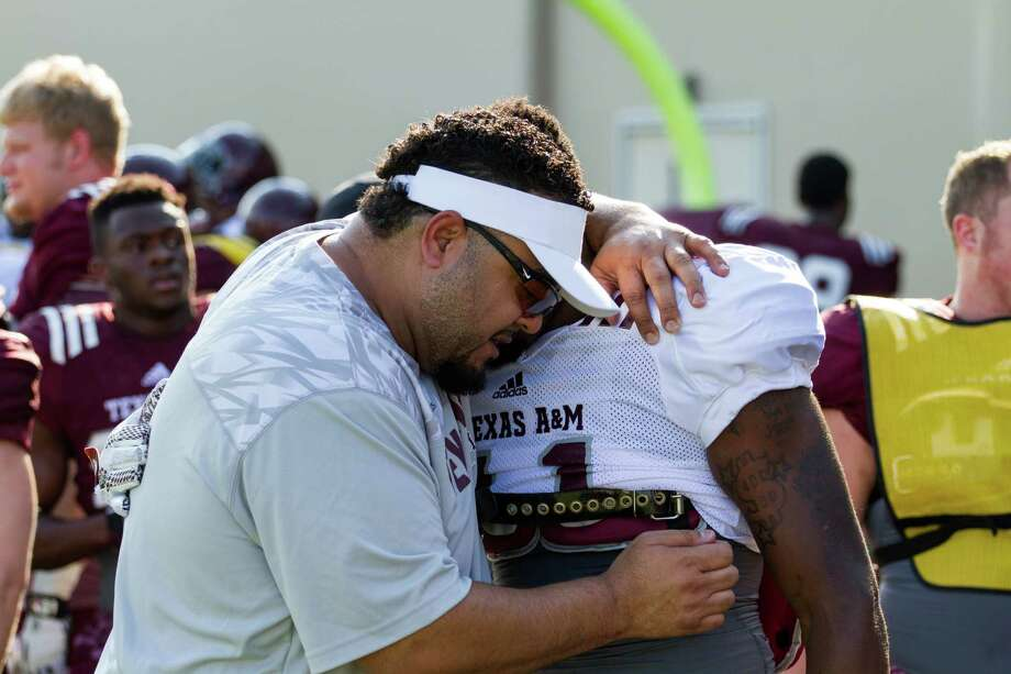 Mikado Hinson prays with Texas A&M football player Josh Walker. Hinson serves as the team's director of player development, acting as a sort of mentor and life coach for the players. Photo: Matt Simon