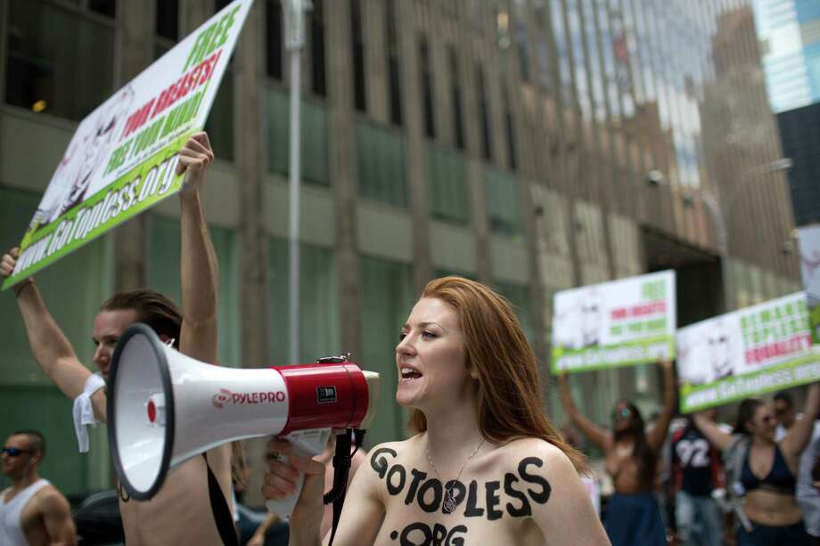 Rachel Jessee speaks into a megaphone while riding atop a car during the GoTopless Day Parade, Sunday, Aug. 23, 2015, in New York. The parade took to the streets to counter critics who are complaining about topless tip-seekers in Times Square. Appearing bare-breasted is legal in New York. But Mayor Bill de Blasio and police Commissioner Bill Bratton say the body-painted women in the square who take photos with tourists are a nuisance. (AP Photo/Kevin Hagen) ORG XMIT: NYKH101 Photo: Kevin Hagen / FR170574 AP