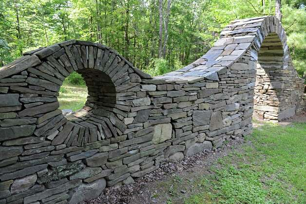 Stone wall with archway on Thom Breitenbach's property where he owns a castle he's made out of local stone which is also a wedding venue on Monday, Aug. 17, 2015 in Altamont, N.Y. He is also an artist and plans to leave the castle and his paintings as a museum when he dies. (Lori Van Buren / Times Union) Photo: Lori Van Buren / 00032981A