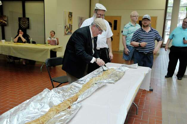 Troy Mayor Lou Rosamilia, left, cuts into what organizers called the worldOs largest knish, as Leible Morrison, second from left, president of the Beth-Tephilah Synagogue looks on at the OTo LifeO Festival put on by the synagogue at the Troy Atrium on Sunday, Aug. 23, 2015, in Troy, N.Y.  The event featured Jewish ethnic foods, music and talks on the religion and culture.    (Paul Buckowski / Times Union) Photo: PAUL BUCKOWSKI / 00033019A